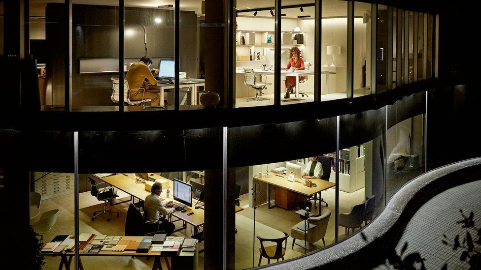 Edificio de oficinas con muchas personas trabajando de noche