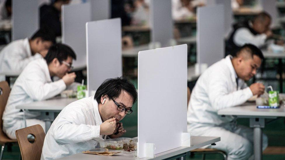 Vuhan'daki Dongfeng Honda'da öğle arasında yemek yiyen işçiler.