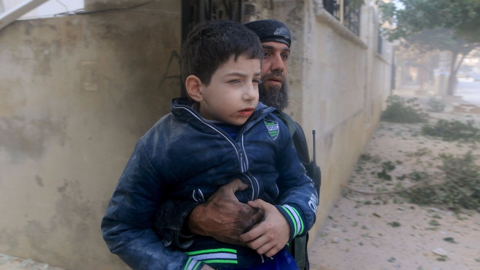 A rescue worker holds an injured boy after what activists said were airstrikes carried out by the Russian air force in Idlib