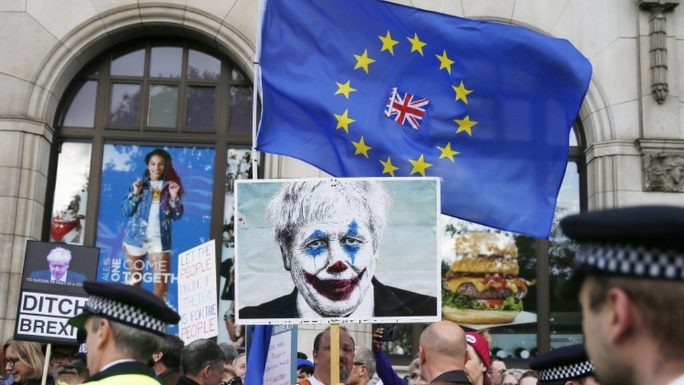 London protester holds up photo of Boris Johnson with clown's make-up, 19 October 2019