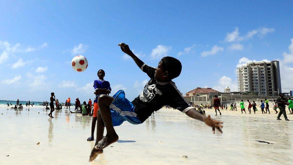 صبي يلعب كرة قدم على الشاطيء