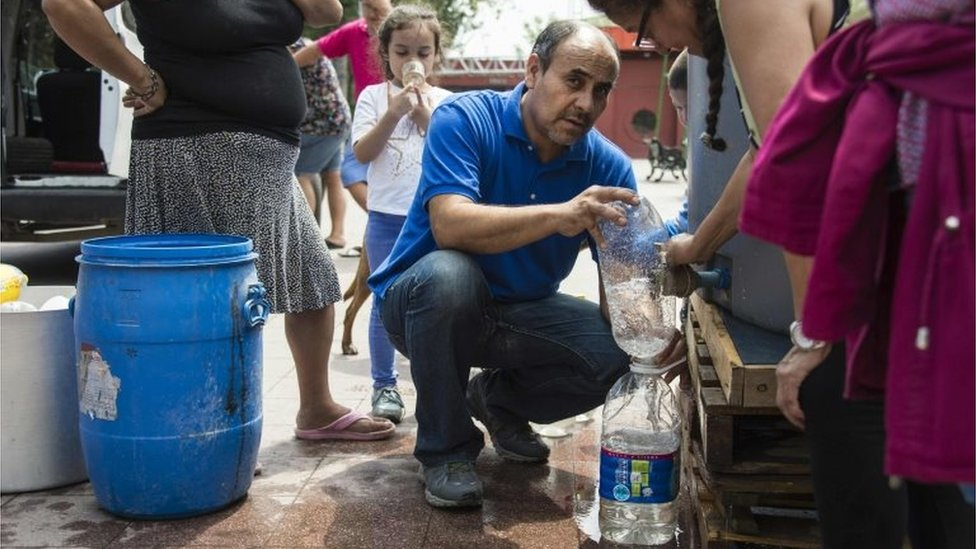 People get water during a drinking water supply cut in Santiago, on February 26, 2017.