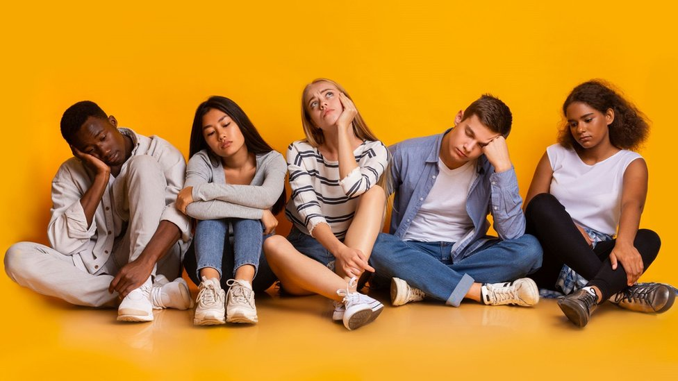 Cinco adultos jóvenes sentados en el suelo