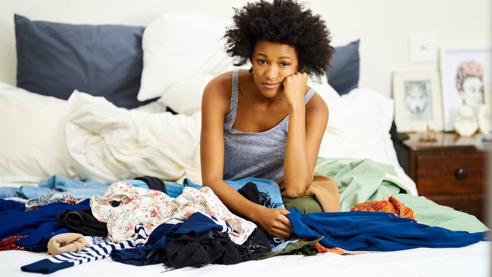 Fed-up young woman on bed surrounded by clothes
