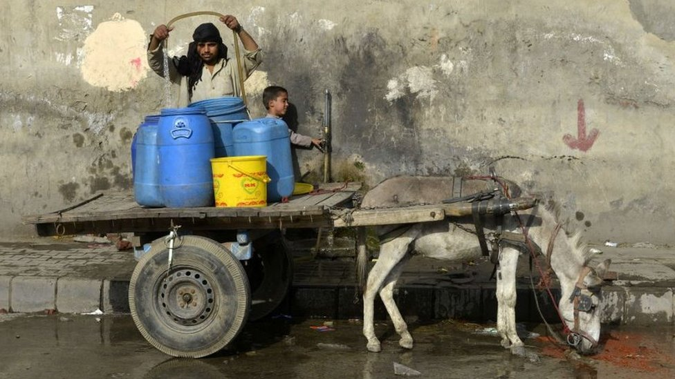 A man fills plastic containers with water on a cart drawn by a donkey