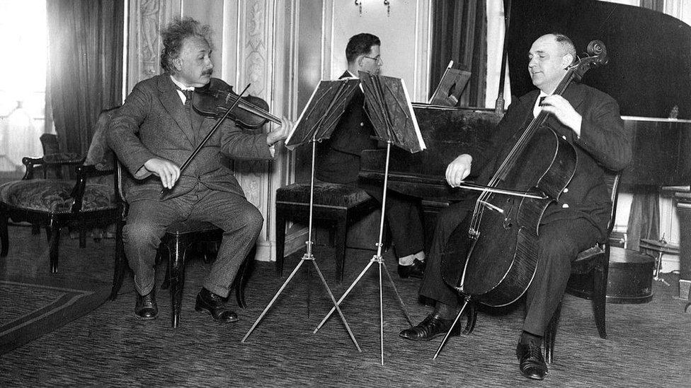 Einstein con otros músicos tocando el violín.