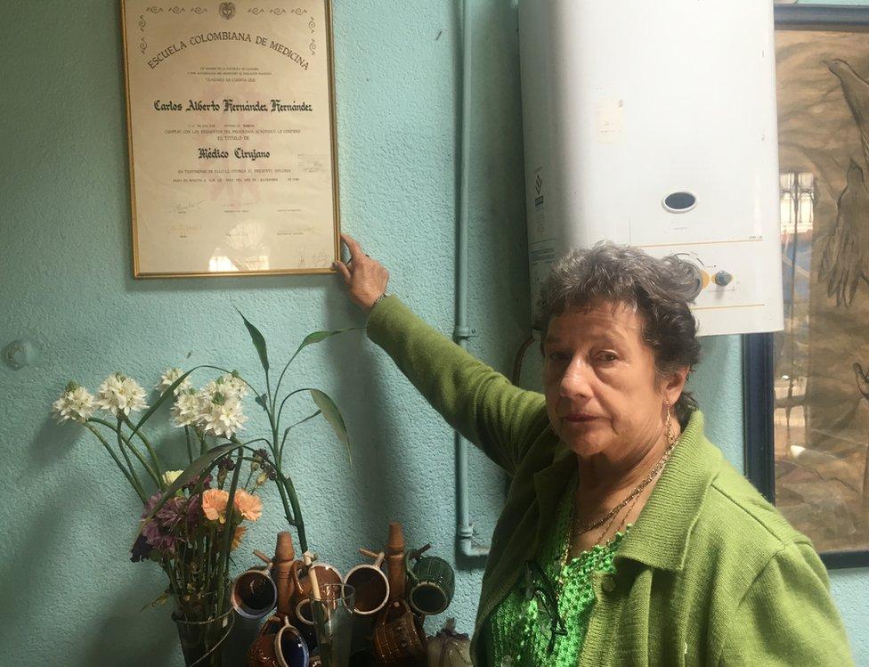 La mujer exhibe con orgullo el diploma de medicina obtenido por su hijo Carlos.