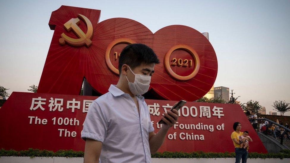 Una persona se toma fotografías frente a un gran cartel del Partido Comunista en Shanghái.