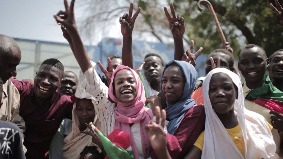 A crowd celebrates outside a venue in Sudan's capital, Khartoum, where generals and protest leaders signed a historic transitional constitution meant to pave the way for civilian rule in Sudan - August 2019