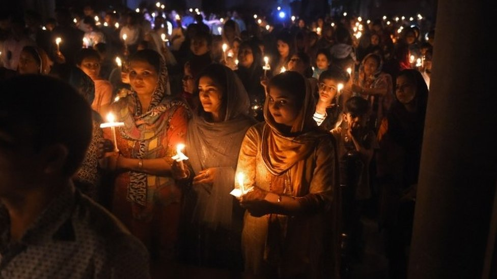 Pakistani Christian devotees holding candles while attending a Easter Vigil Mass at the Sacred Heart Church in Lahore.