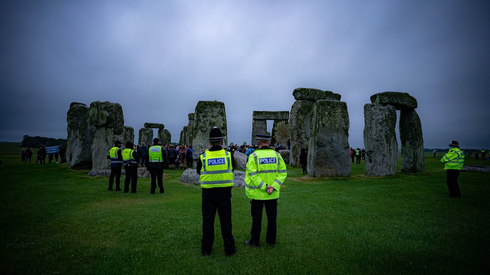 Police watch crowds celebrate during Summer Solstice at Stonehenge, where some people jumped over the fence to enter the stone-circle to watch the sun rise at dawn of the longest day in the UK.