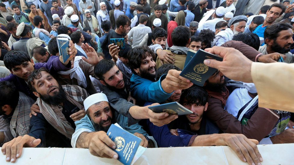 A crowd of men holding up their passports