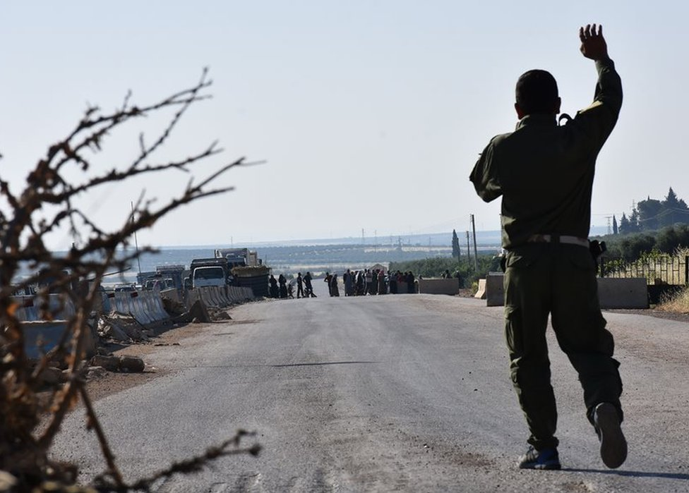 A fighter from the Kurdish People's Protection Units (YPG) gestures at displaced Syrians walking towards a Kurdish controlled checkpoint between the rebel-held town of Azaz in northern Syria and the city of Afrin, along Syria's northern border with Turkey, as they attempt to cross in June 2017