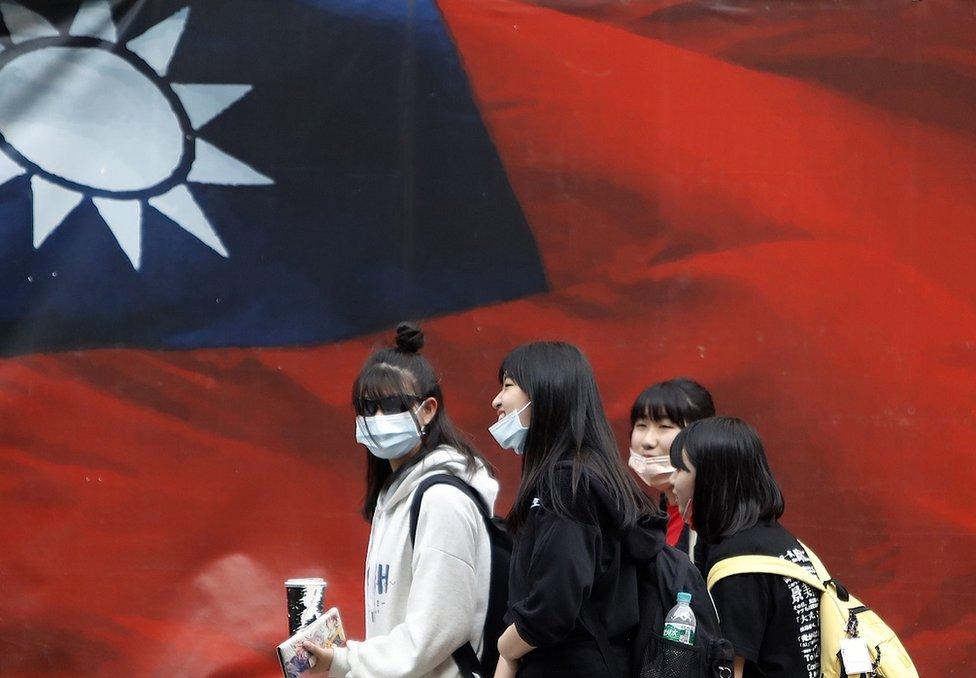戴著口罩的台灣女生走過中華民國國旗(2021年4月11日資料照片)