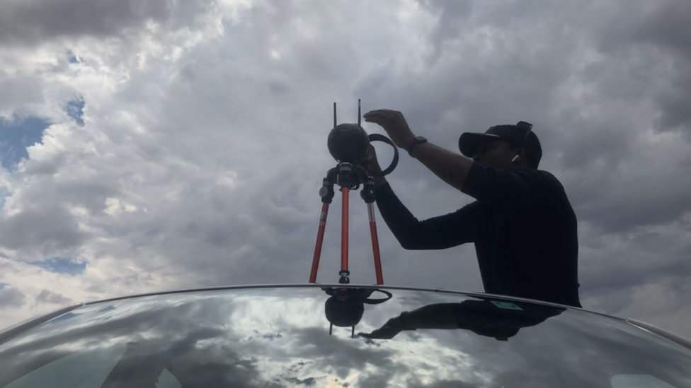 Tawanda fixing his camera on top of a car