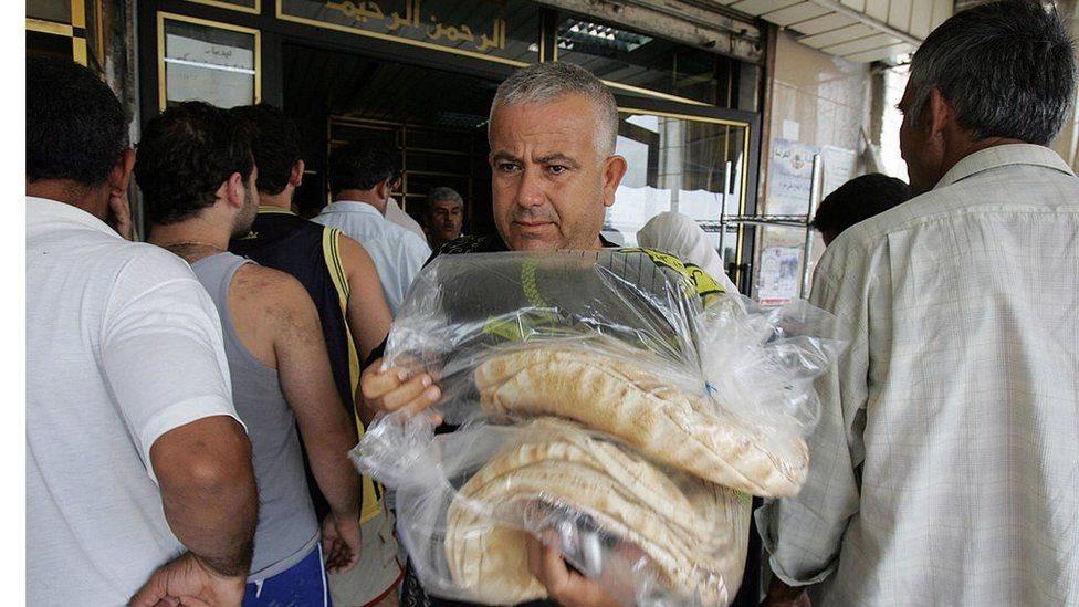 رجل يحمل خبزا وسط زحام من الناس أمام أحد المخابز