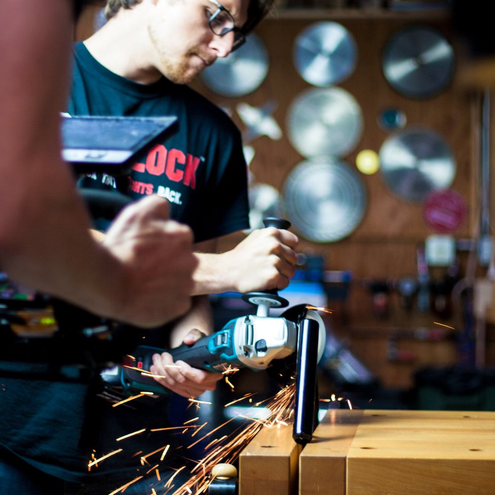 Daniel, one of the co-founders, shown attempting to cut through the Skunklock prototype with an angle grinder