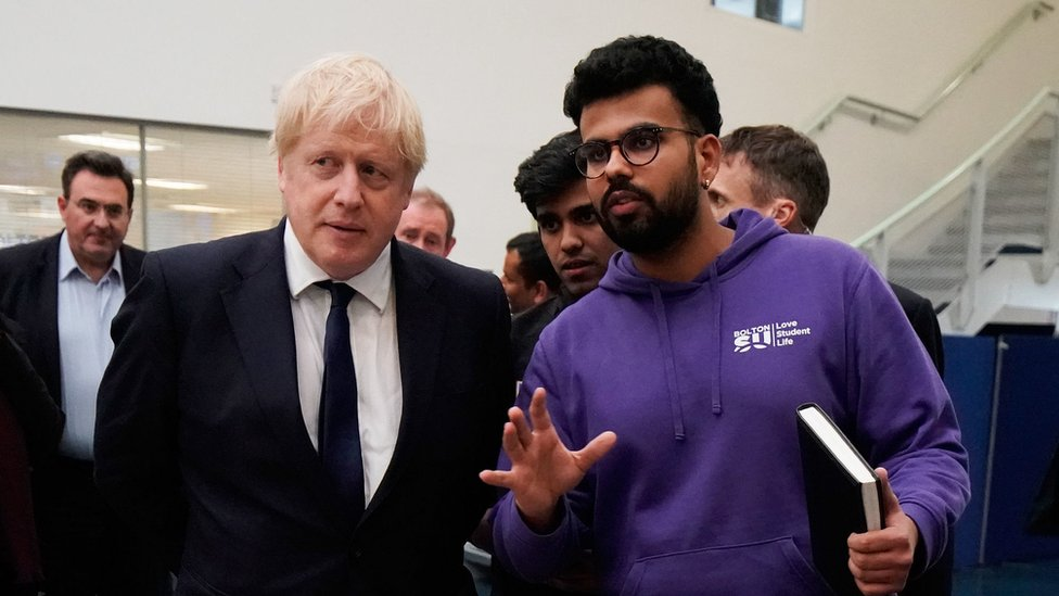 Prime Minister Boris Johnson speaks to a student during a visit to Bolton University chancellors building after a huge blaze