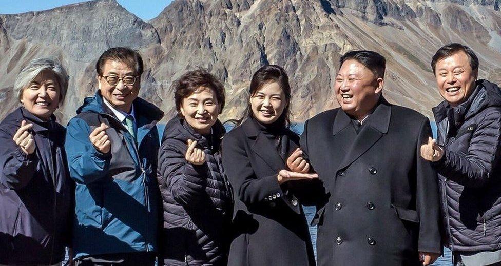 Los presidentes de Corea del Norte y Sur junto a otras personas forman un símbolo del corazón con los dedos.