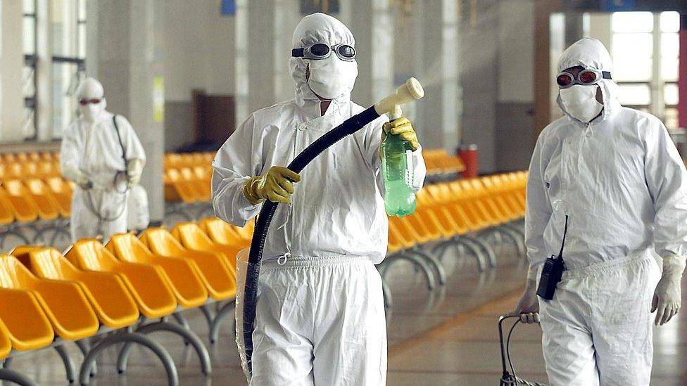 Dos trabajadores limpian la estación de tren de Pekín en pleno brote del SARS en China, en 2003.