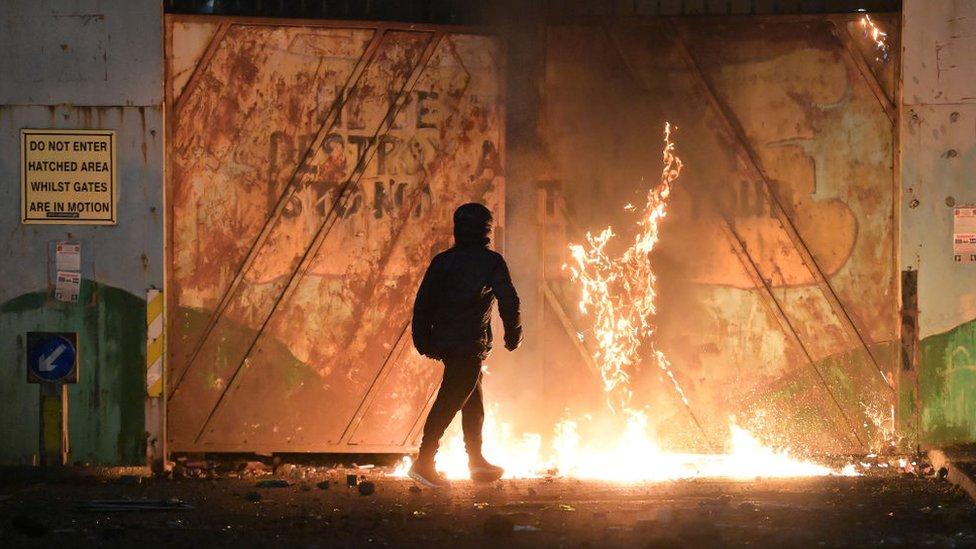 Joven ante un incendio en las protestas en Irlanda del Norte