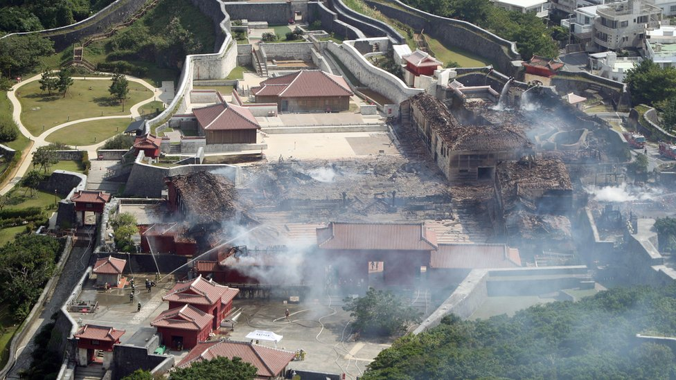 An aerial photograph shows the destroyed Shuri Castle in Naha