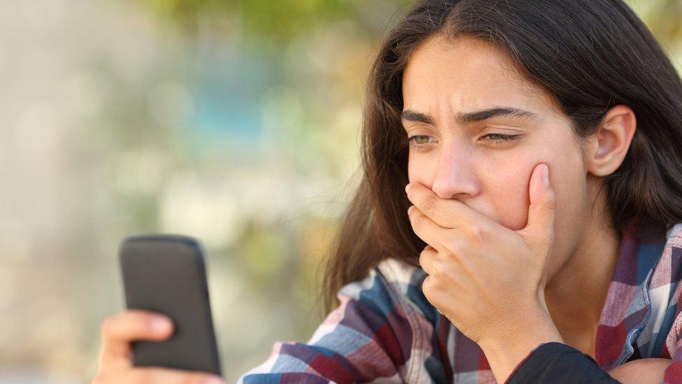 A worried-looking teenager looking at mobile phone
