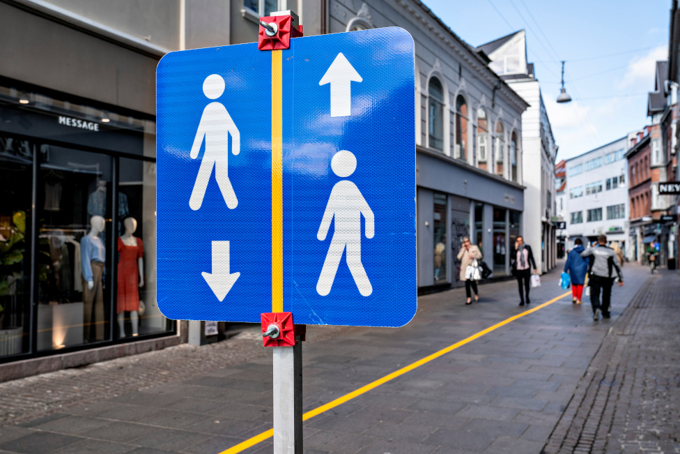 A yellow stripe is painted in the middle of a pedestrian street to help people comply with the social distance guidelines