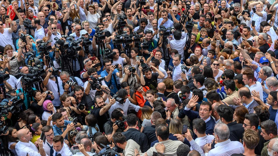 Opposition candidate Ekrem Imamoglu (lower right, looking towards camera) waves after leaving polling station - 23 June