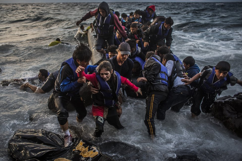 Refugees arrive on the shores of the Greek island of Lesbos after crossing the Aegean sea from Turkey on an inflatable boat, 1 October 2015