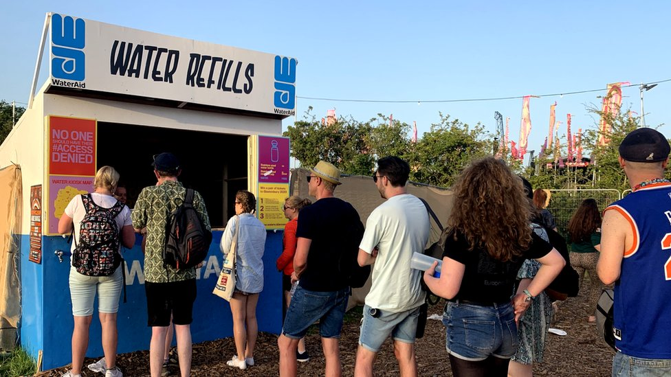 Festival-goers queue for water
