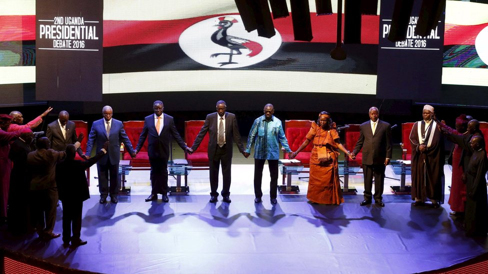 Uganda's presidential candidates hold hands as they pray before a presidential debate in Kampala