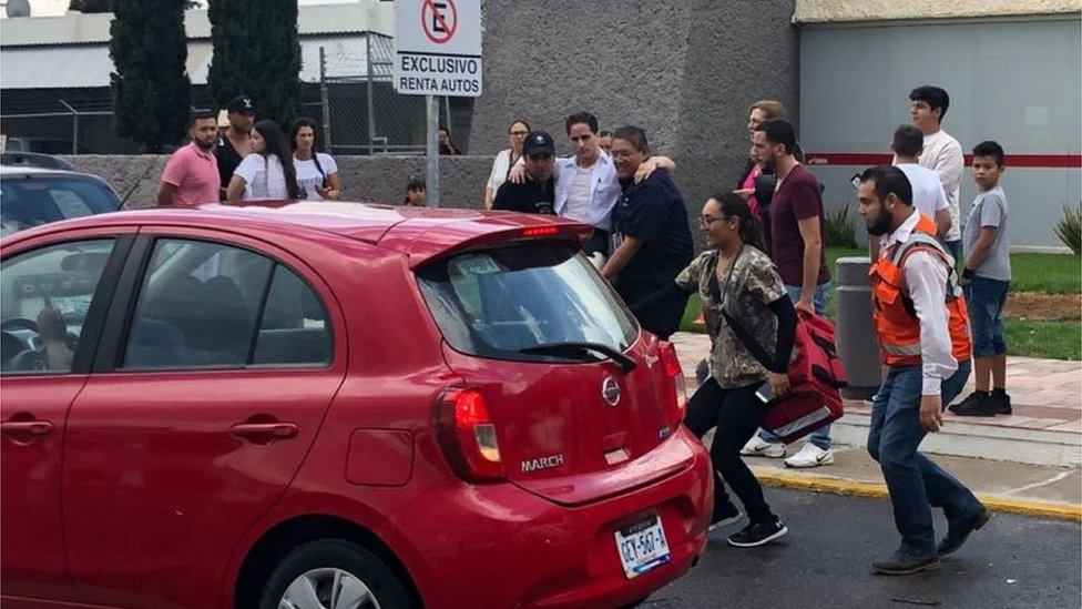 Picture released by Contacto Hoy showing a man (C) being rushed into a vehicle at the airport of Durango, in northern Mexico, after a plane carrying 97 passengers and four crew crashed on take off near the city's airport on July 31, 2018.