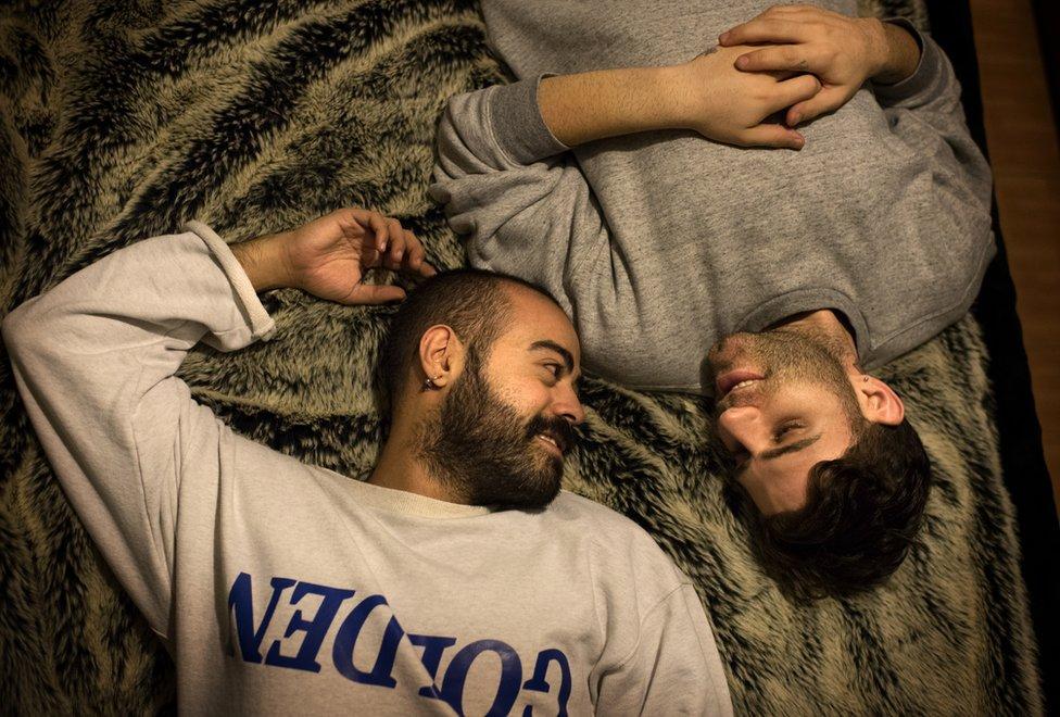 Elias lies on a bed with his boyfriend Marwan