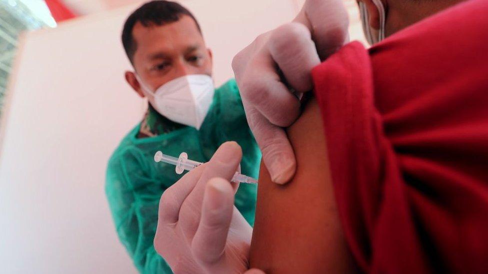 2021年6月26日,一名印尼軍醫在雅加達進行的新冠疫苗接種推廣活動中為一名男士注射由Biofarma公司生產的科興疫苗。