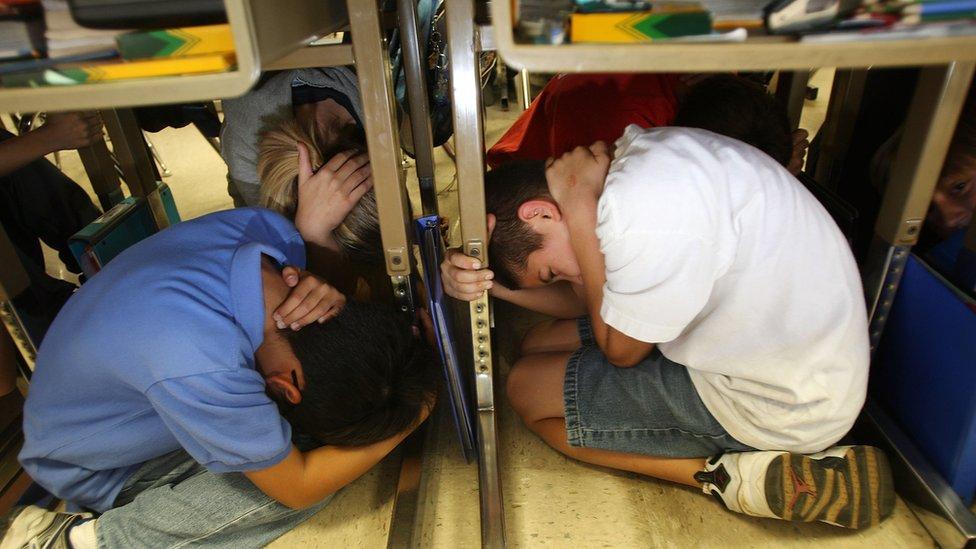 Two children crouch under their desks