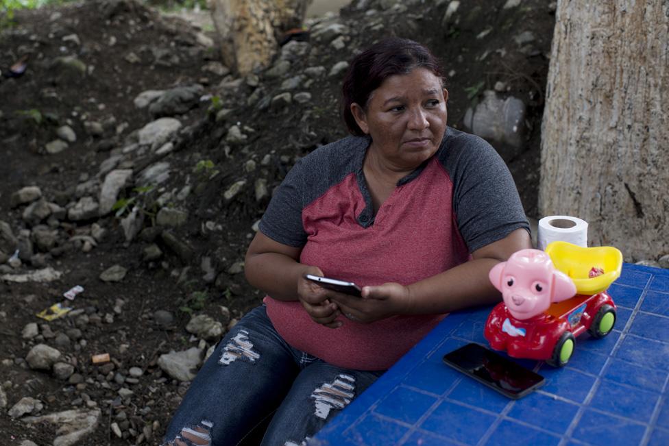 Sandra Pérez Maldonado sits at a table outside her mother's home