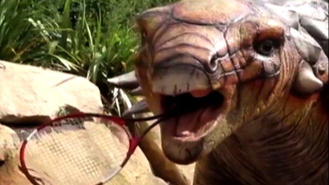 An animatronic dinosaur at Edinburgh Zoo holding a tennis racquet