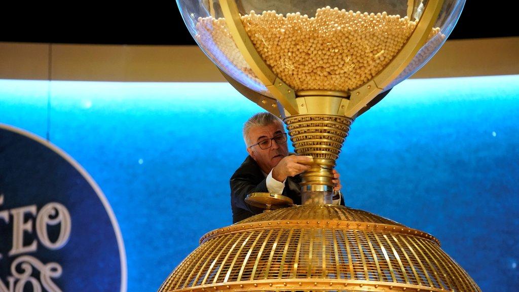 Las pelotas de la lotería se lanzan a una esfera rotante antes del inicio del Sortero Extraordinario de Navidad, en Madrid
