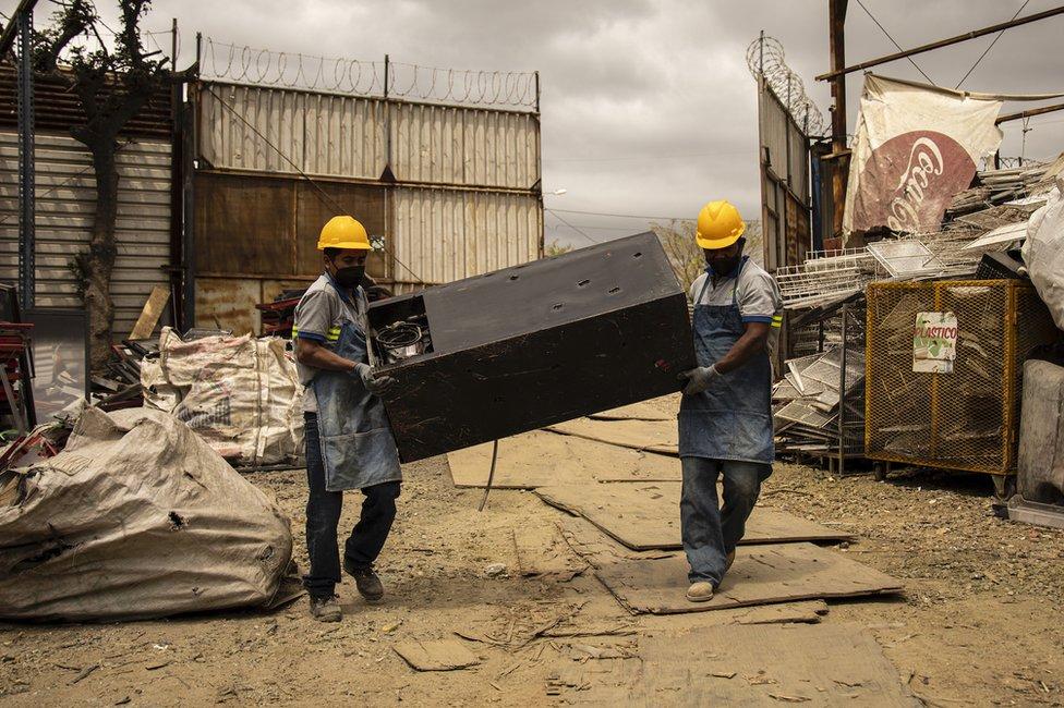 Trabajadores cargan una nevera vieja en las afueras de Ciudad de Guatemala.