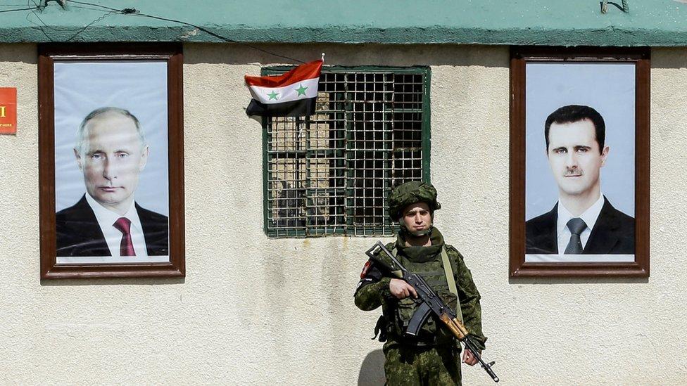 جندي من الجيش الروسي يقف خارج بناية في سوريا عليها صورتين لفلاديمير بوتين وبشار الأسد