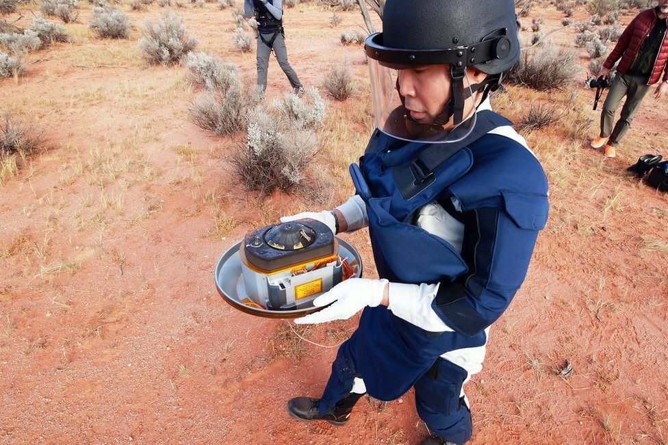 A team member carries the capsule, which contains samples from an asteroid