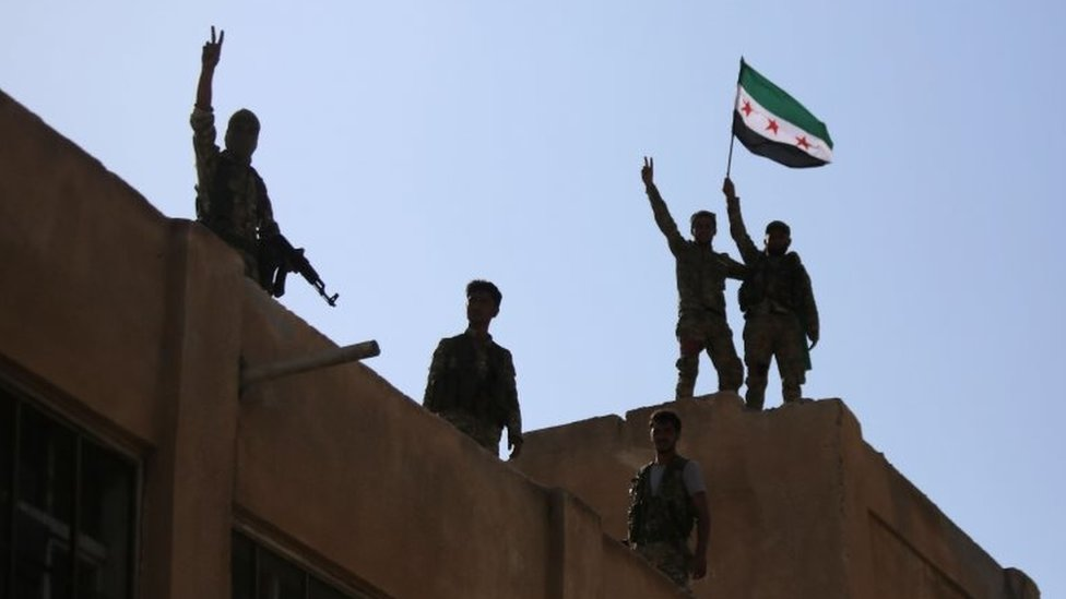Turkish-backed Syrian fighters wave the Syrian opposition flag on top of a building in the south-western neighbourhoods of the border town of Tal Abyad on 13 October 2019