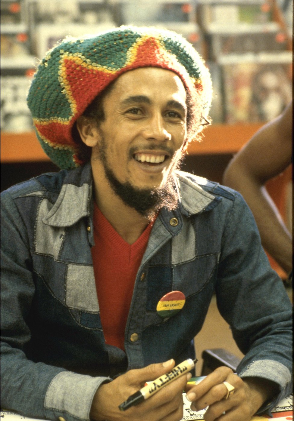 Bob Marley sits at a table holding a pen