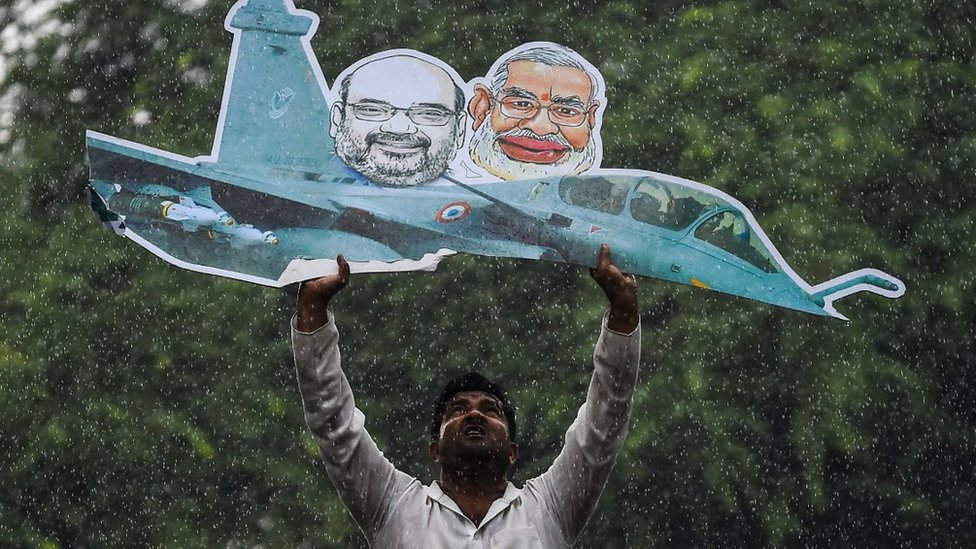 A supporter of the Indian Youth Congress holds a model of a Rafale fighter jet as he gets detained by Indian police during a protest in New Delhi on September 22, 2018.