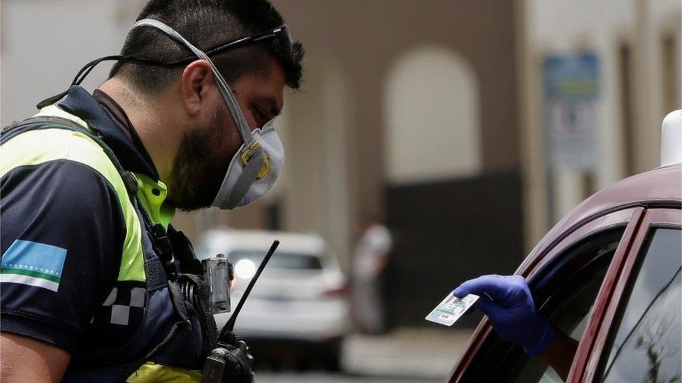 Un policía inspeccionando a un automovilista