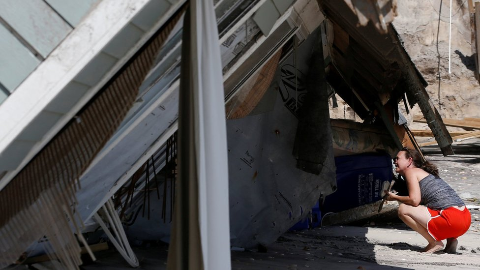 A local resident looks inside a collapsed coastal house after Hurricane Irma passed the area in Vilano Beach, Florida