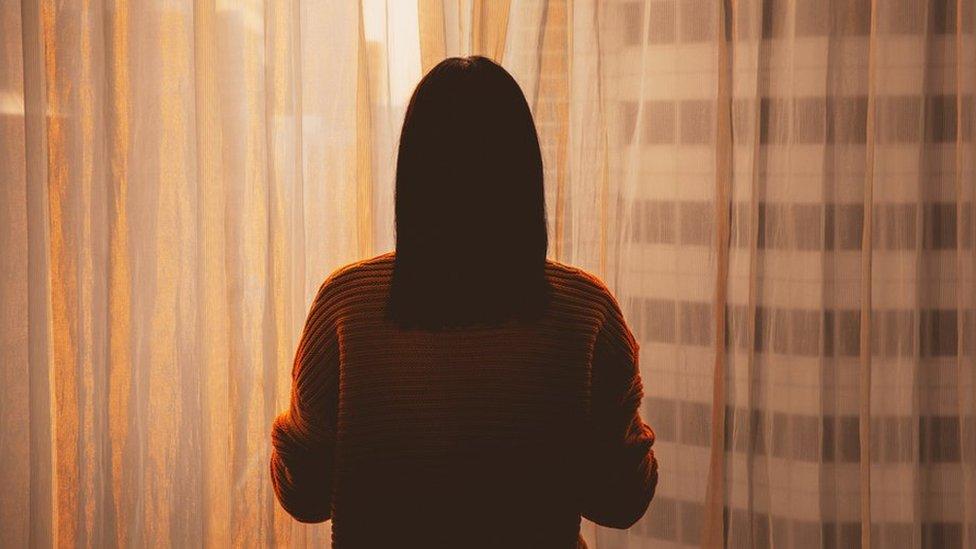 Mujer en Corea del Sur mirando la ventana