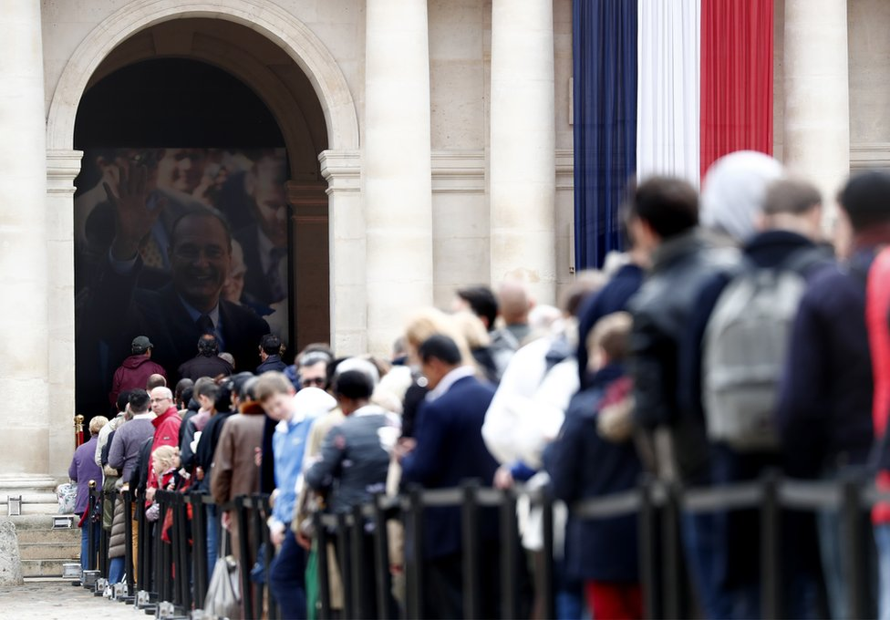 Visitors wait to view the coffin of former French President Jacques Chirac as it lies in state in the Invalides on 29 September 2019.