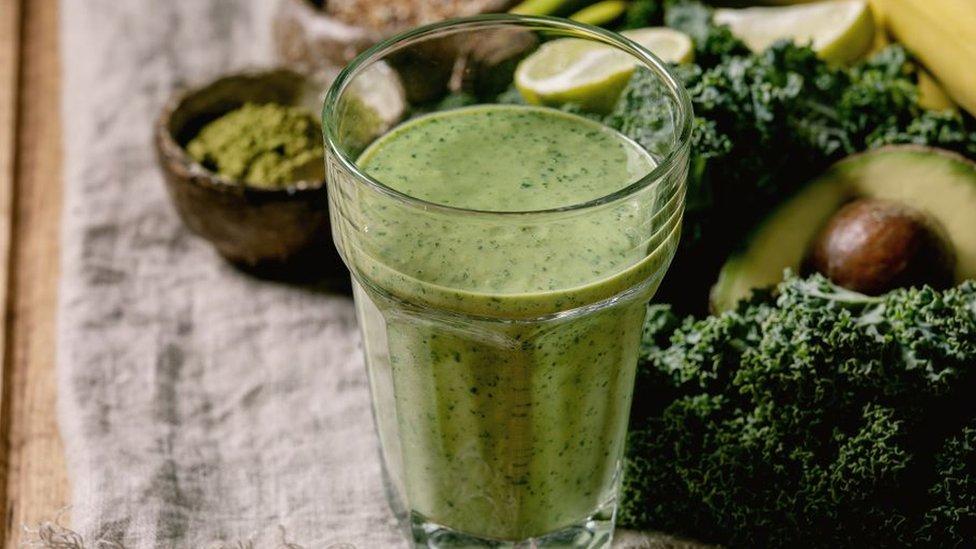 Surtido de alimentos estacionales, incluyendo col rizada, espirulina y aguacate